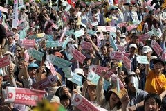 """Participants raise banners with a slogan, """"Good bye, nuclear power station""""."""