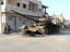 Syrians next to a destroyed and abandoned army tank on March 10 in the Syrian town of Rastan