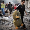 A Palestinian man carries a stuffed toy after an Israeli air raid on a nearby sporting centre in Gaza City (AFP)