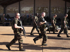 French soldiers walk past a hangar at the Malian army air base in Bamako
